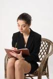 在笔记本的女商人文字 免版税库存照片