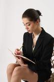 在笔记本的女商人文字 库存照片