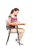 在笔记本的女学生文字 免版税库存照片