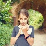在笔记本的小女孩图画在曲拱桥梁附近 免版税库存照片