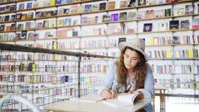 在笔记本的年轻女人文字在图书馆里 股票录像
