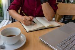 在笔记本的年轻女实业家文字经营计划在咖啡馆 免版税库存照片