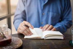在笔记本的成人自由职业者的商人文字 免版税库存照片