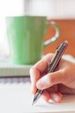 在笔记本的手writng在咖啡店 免版税库存照片