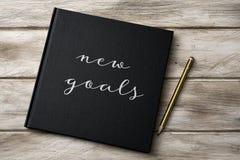 在笔记本的文本新的目标 库存照片