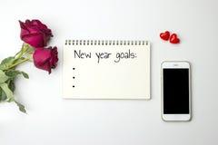 在笔记本的新的year' s目标词有玫瑰和巧妙的电话的 库存图片