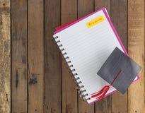 在笔记本的毕业盖帽反对木背景 免版税库存图片