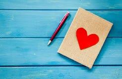 在笔记本的爱心脏有笔的 免版税库存图片
