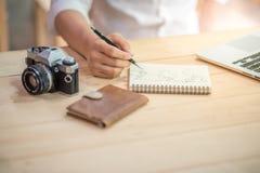 在笔记本的男性手文字世界概述 免版税库存照片