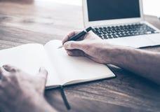 在笔记本的男性收养文字除在木书桌上的便携式计算机以外 免版税库存照片