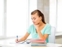 在笔记本的疲乏的学生文字 免版税图库摄影