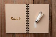 在笔记本的盐瓶 库存图片