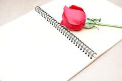 在笔记本的红色玫瑰 库存图片