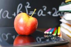 在笔记本的红色苹果有书架的 库存照片