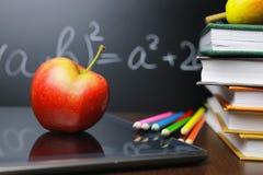 在笔记本的红色苹果有书架的 免版税图库摄影