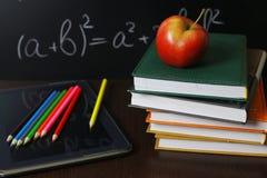 在笔记本的红色苹果有书架的 免版税库存图片