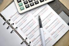 在笔记本的计算器有笔的 免版税库存图片
