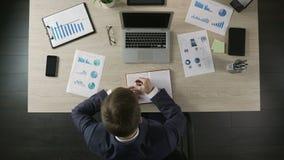 在笔记本的负责任的商人文字,做计划目录,时间安排 股票录像