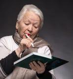 在笔记本的资深妇女文字笔记 免版税库存照片