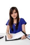 在笔记本的年轻亚洲妇女文字在一张桌上,在白色 库存图片