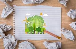 在笔记本纸的Eco友好的地球与铅笔 免版税库存图片