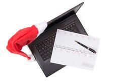 在笔记本计算机上的红色圣诞老人帽子 库存图片