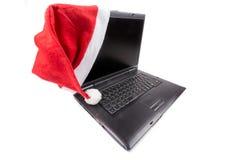 在笔记本计算机上的红色圣诞老人帽子 库存照片