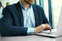 在笔记本计算机,工作场所的企业人上的人的手 免版税库存照片