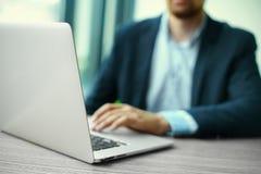 在笔记本计算机,工作场所的企业人上的人的手 免版税图库摄影