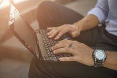在笔记本键盘的男性手 库存图片