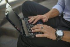 在笔记本键盘的男性手 免版税图库摄影
