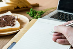 在笔记本顶部的一个人候宰栏 工作表包括膝上型计算机、笔记本和早餐用切的面包与chocolat 库存图片