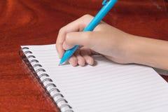 在笔记本,木backgroud的手文字 免版税图库摄影