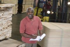 在笔记板的老人文字有驾驶Forktruck的人的在仓库 库存照片