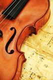 在笔记背景的老小提琴  免版税库存照片