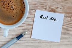 在笔记薄写的以下步骤题字在早晨咖啡杯附近 事务,技术,互联网概念 图象纵向股票妇女年轻人 免版税库存图片