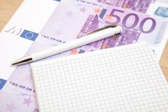 在笔记薄旁边的五百欧洲笔记 免版税库存照片