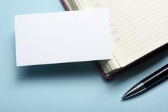 在笔记薄的名片空白在办公室桌上 公司文具烙记的大模型 库存图片