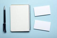 在笔记薄的名片空白在办公室桌上 公司文具烙记的大模型 库存照片