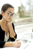 在笔记薄的妇女文字在桌上 免版税库存图片