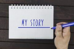 在笔记薄的手文字:我的故事 免版税库存照片