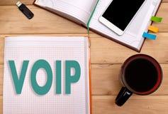在笔记薄的笔记VOIP在商人的书桌上 免版税库存照片