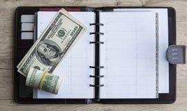 在笔记薄的美金 砖灰色纸棍子磁带墙壁白色 背景美元查出我们空白 嘲笑 库存图片