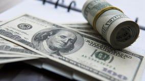 在笔记薄的美金 砖灰色纸棍子磁带墙壁白色 背景美元查出我们空白 库存照片