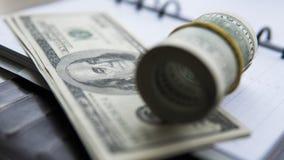 在笔记薄的美金 砖灰色纸棍子磁带墙壁白色 背景美元查出我们空白 库存图片