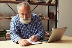 在笔记薄的老人文字在他的工作地点 免版税库存图片
