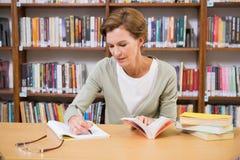 在笔记薄的老师文字在图书馆 免版税库存图片