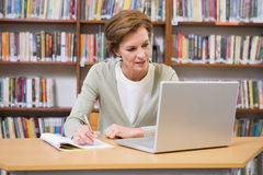 在笔记薄的老师文字在图书馆 免版税库存照片