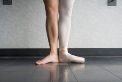 在第一个位置的跳芭蕾舞者与一只脚在pointe鞋子和一条光秃的腿 免版税库存照片