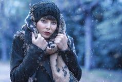 在第一冬天雪期间的一个年轻和美丽的女孩 免版税库存照片